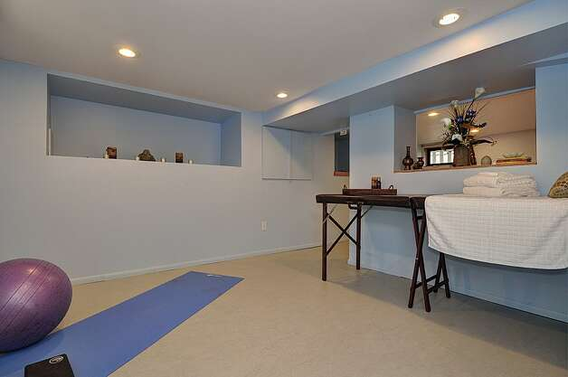 Lower-level rec room of 3032 Walnut Ave. S.W. The 1,340-square-foot house, built in 1924, has two bedrooms, one bathroom, coved ceilings, office with built-in desk and Murphy bed, attic room, rear deck and a hot tub on a 3,440-square-foot lot. It's listed for $385,000. Photo: Courtesy Gini Johnson/Prudential Northwest Realty