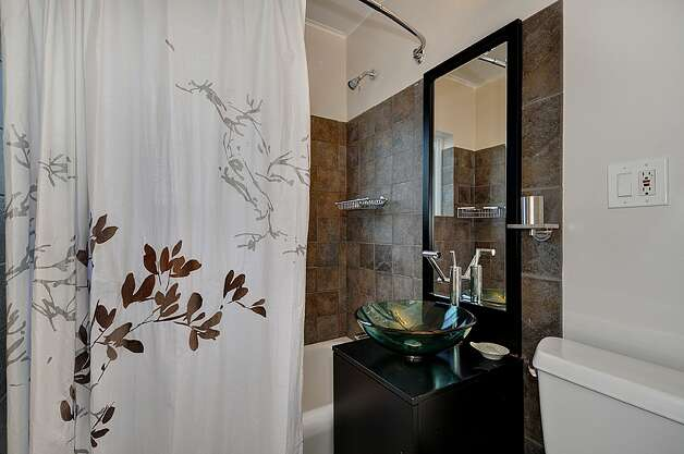 Bathroom of 3032 Walnut Ave. S.W. The 1,340-square-foot house, built in 1924, has two bedrooms, one bathroom, coved ceilings, office with built-in desk and Murphy bed, lower-level rec room, attic room, rear deck and a hot tub on a 3,440-square-foot lot. It's listed for $385,000. Photo: Courtesy Gini Johnson/Prudential Northwest Realty