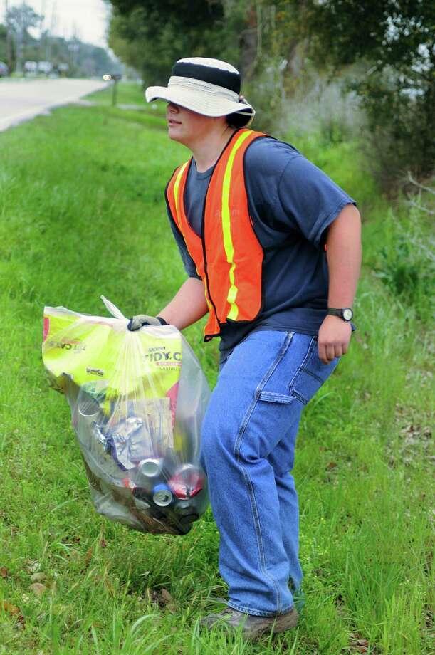 Vincent Sclider carries a bag full of trash along Telge Road. Photo: David Hopper / freelance