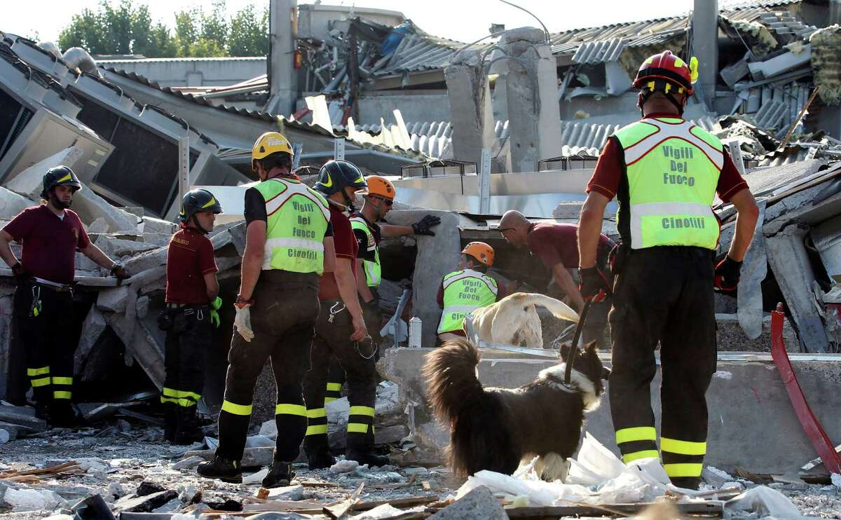 Rescue teams use dogs as they look for three workers reported missing at the Haemotronic factory in Medolla, northern Italy, Tuesday. A magnitude 5.8 earthquake struck the same area of northern Italy stricken by another fatal tremor on May 20.