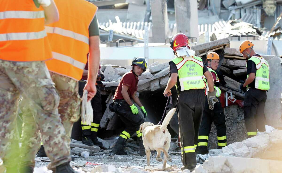Rescue teams use dogs as they look for three workers who are reportedly missing at the Haemotronic factory in Medolla, northern Italy, Tuesday A magnitude 5.8 earthquake struck the same area of northern Italy stricken by another fatal tremor on May 20.