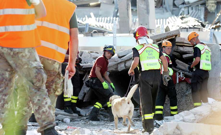 Rescue teams use dogs as they look for three workers who are reportedly missing at the Haemotronic factory in Medolla, northern Italy, Tuesday A magnitude 5.8 earthquake struck the same area of northern Italy stricken by another fatal tremor on May 20. Photo: Luca Bruno, AP / AP2012