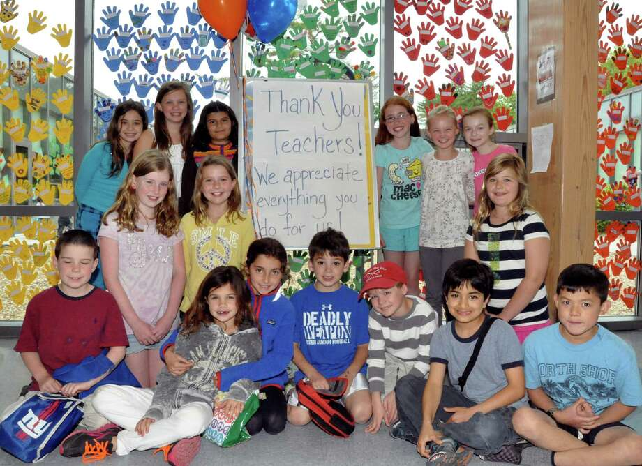 Pictured are Tokeneke School second and fourth graders in front of the rainbow-colored display of their hand-made hands of appreciation recently in Darien, Conn. Photo: Contributed Photo