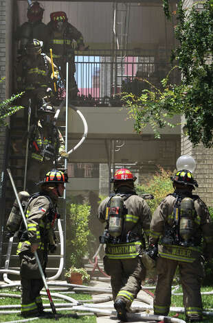 San Antonio firefighters climb down stairs from a second story breezeway at the Devonshire Condominiums after a two alarm fire broke out there about 1 p.m. in building number 14. The fire broke out at the condos at 11843 Braesview after maintenance workers conducting plumbing repairs accidentally set a wall on fire. The fire has temporarily displaced five families. Photo: San Antonio Express-News