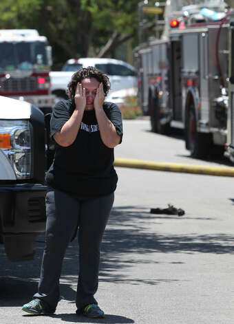 A distraught woman stands in front of fire trucks Tuesday after a two alarm fire broke out about 1:00 p.m. at the Devonshire Condominiums at 11843 Braesview. Assistant Fire Chief Robert Mikel said maintenance workers accidentally set a wall on fire while attempting plumbing repairs. No injuries were reported at the fire. Photo: San Antonio Express-News