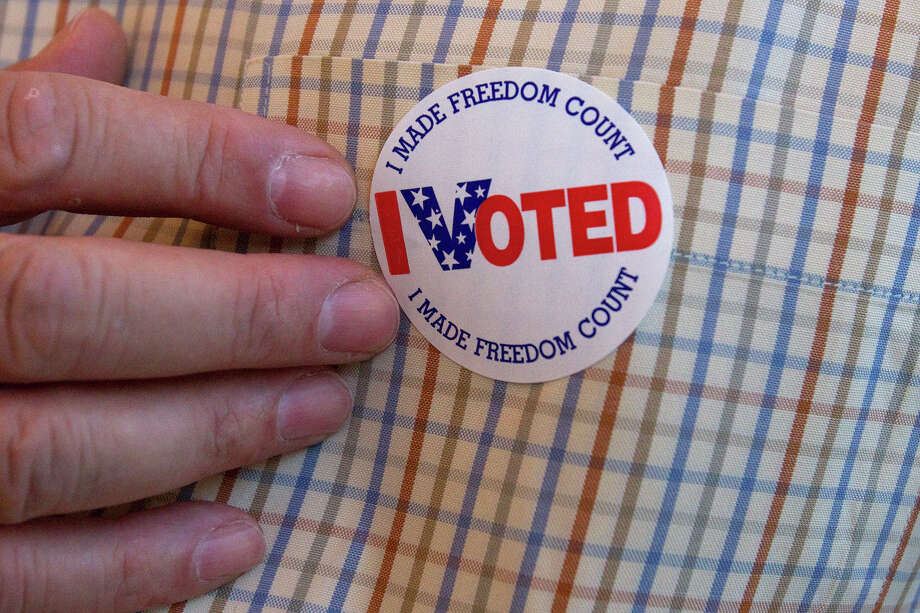 Tim McDavid touches his voting sticker after voting at the Metropolitan Multi-Services Center Tuesday, May 29, 2012, in Houston. (Cody Duty / Houston Chronicle) Photo: Cody Duty / © 2011 Houston Chronicle