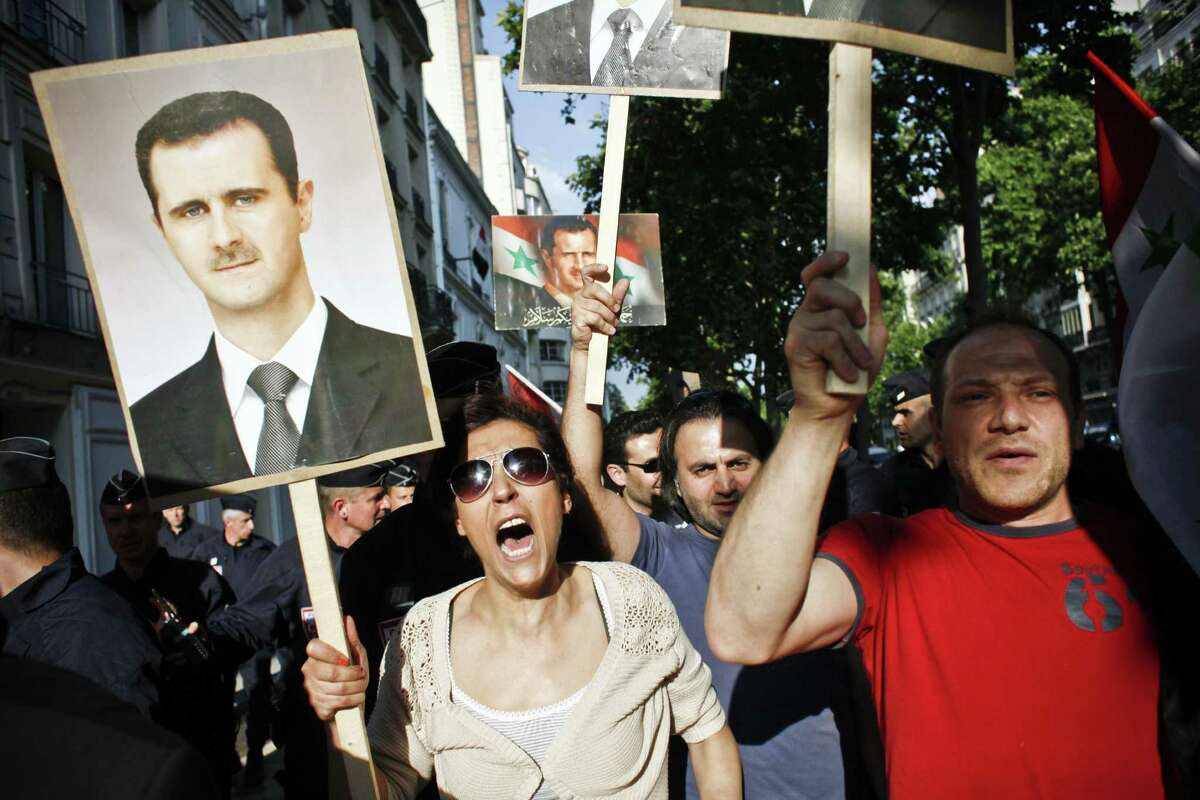 Supporters of the regime hold portraits of President Bashar al-Assad during a rally in Paris. France was one of the nations booting out Syrian diplomats.