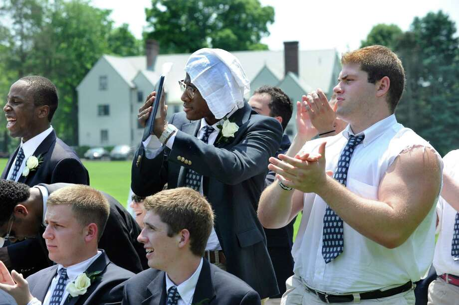 Nick Hough, standing center and John Jednorowicz, right, find their own ways to deal with the brutal heat at Canterbury School's graduation ceremony Tuesday, May 29, 2012 in New Milford, Ct. Photo: Carol Kaliff / The News-Times