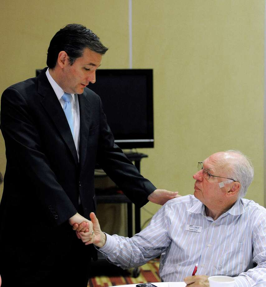 Texas US Senate Republican primary candidate Ted Cruz, left, talks with his father Rafael Cruz as he works at the campaign's phone bank, on election day, Tuesday, May 29, 2012, in Houston. (AP Photo/Pat Sullivan) Photo: Pat Sullivan / AP