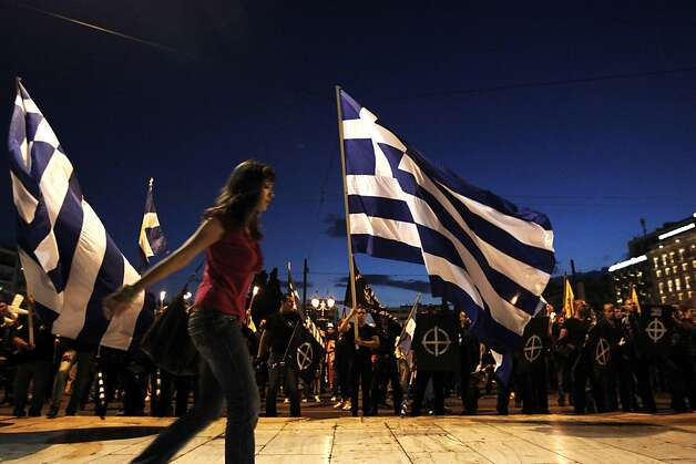 A woman walks past supporters of the Greek far-right party Chryssi Avghi (Golden Dawn) during a march in front of the Greek Parliament commemorating the fall of Constantinople, the capital of the Byzantine empire, in Athens, May 29, 2012. Immigrants abound in the neighbourhood around Athens' Agios Panteleimon church, but for now they are keeping out of sight. Washed up here after fleeing poverty and violence in Asia and Africa, they now face beatings, insults and exclusion fuelled by Greece's own economic hardship. AFP PHOTO / STRSTR/AFP/GettyImages Photo: Str, AFP/Getty Images