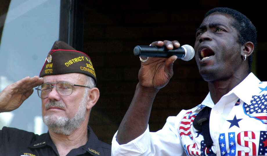 Curtis Thompson belts out a stirring rendition of The Star Spangled Banner as Veterans Committee mamber James DeLancy holds a salute during New Milford's pre-parade Memorial Day ceremony. May 28, 2012 Photo: Norm Cummings