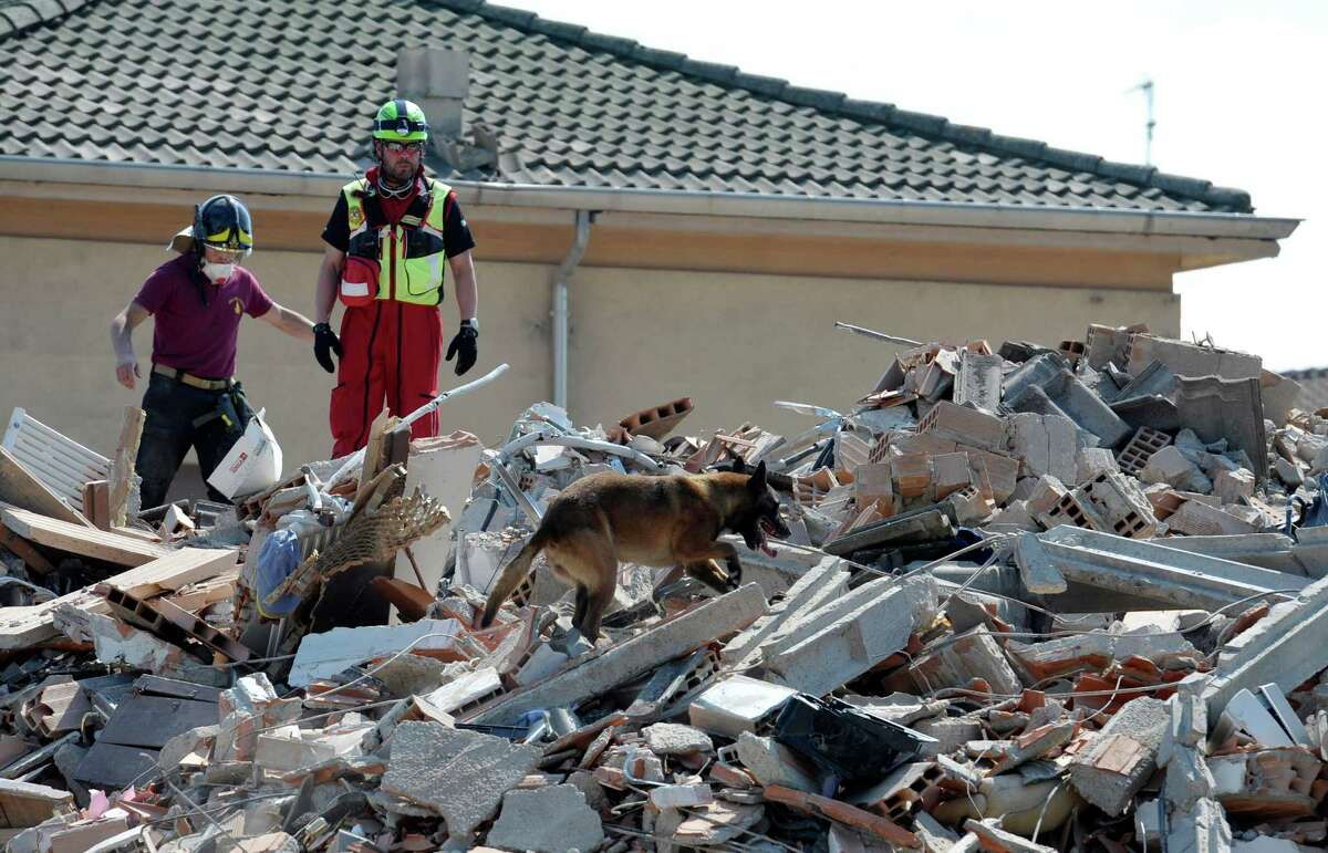 Italian firefighters and a dog search the debris of a collapsed house Tuesday in Cavezzo, northern Italy, after a powerful temblor killed at least 16 people as it rocked a region not previously considered quake-prone.