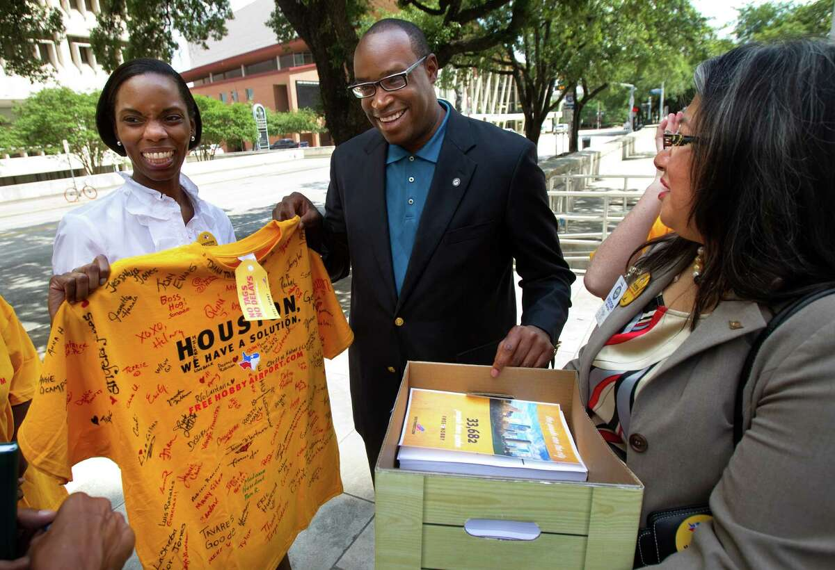 Angela Jones, left, and Christine Ortega present a T-shirt to Councilman Larry Green on Tuesday covered with signatures in favor of Southwest Airlines international flights.