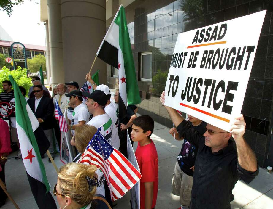 Demonstrators march outside the Bob Casey Federal Courthouse during a news conference condemning the Syrian government Tuesday, May 29, 2012, in Houston. Rep. Sheila Jackson Lee, D-Houston, and members of the local Syrian-American community spoke out against the violence in Syria. The latest round of violence in Syria took place over the weekend, where a reported 108 civilians were killed. ( Brett Coomer / Houston Chronicle ) . Photo: Brett Coomer, Houston Chronicle / © 2012 Houston Chronicle