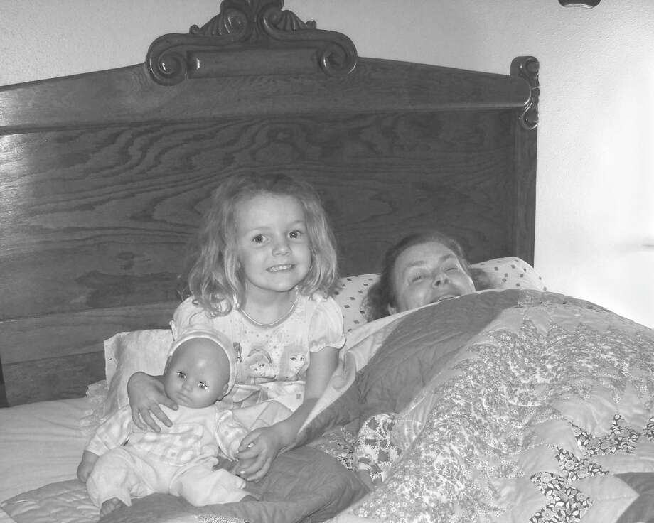 Charlotte Hirt, her granddaughter, Grayci Marie Jung, 5, and Grayci's doll, Sarah in Fredericksburg in the bed Charlotte's grandparents were given for their wedding in 1915. Photo: COURTESY