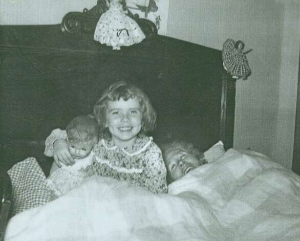 "Anna Hansen, her granddaughter Charlotte Hirt, 5, and Charlotte's doll Betty, in San Antonio, 1955. From Charlotte Hirt: ""The bed we are in was given to my grandmother and grandfather for their wedding in 1915."" Photo: COURTESY"