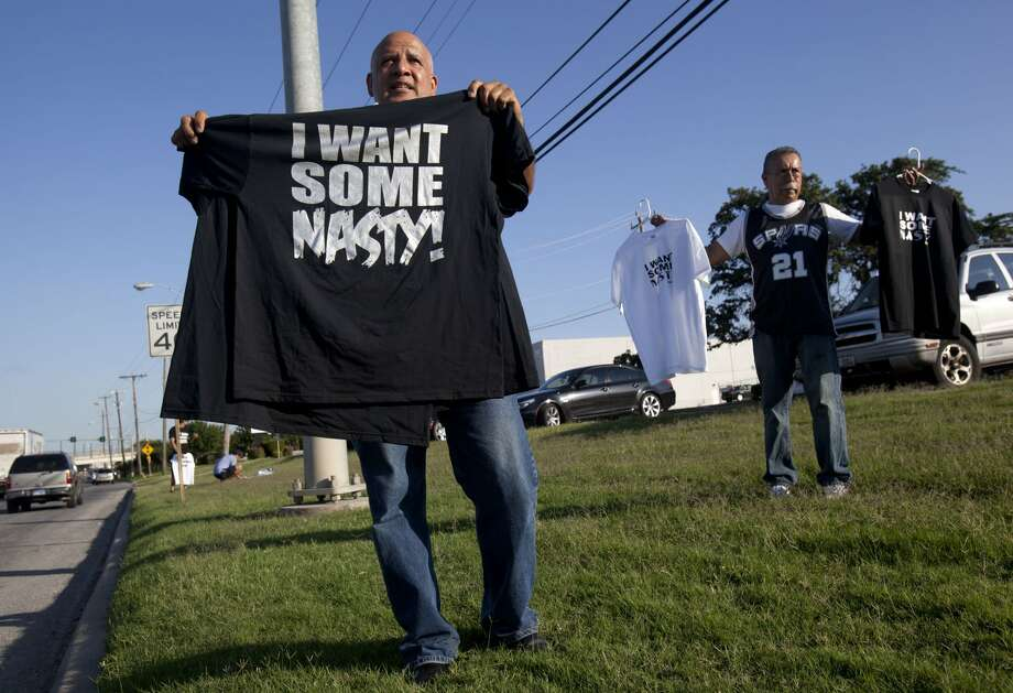 "Javier Hernandez (left) and Louie Torres sell ""I Want Some Nasty"" T-shirts near a Valero gas station on AT&T Center Parkway before Game 2 of the Western Conference Finals in San Antonio on Tuesday, May 29, 2012. Both men bought several shirts for $5 a piece and sold them for $20. ""Let's get on the bandwagon, everybody's talking about it,"" Hernandez said about the decision to sell the shirts. (Julysa Sosa / San Antonio Express-News)"