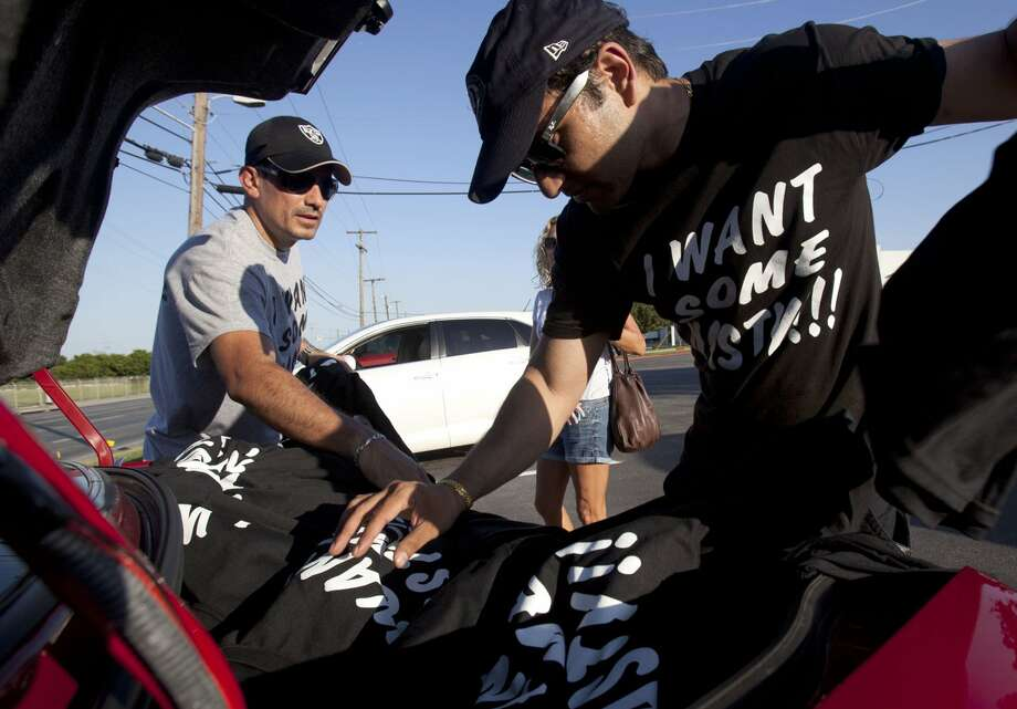 "Alex Nenchaca (left) and Jay Chaudhuri pull ""I Want Some Nasty"" T-shirts from a car trunk to sell before Game 2 of the Western Conference Finals in San Antonio on Tuesday, May 29, 2012. The men bought 500 shirts to sell for $20 each, and sold 150 in an hour. (Julysa Sosa / San Antonio Express-News)"