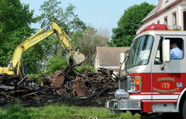 A power shovel reduces 942 State Street in Schenectady, N.Y. to rubble May 29, 2012 after a Sunday fire gutted the building.  The fire is under investigation.  (Skip Dickstein / Times Union) Photo: SKIP DICKSTEIN / 00017860A