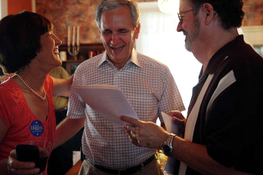 U.S. Rep Lloyd Doggett, center, and his wife, Libby, smile as they get good news about  early voting results from Bob Comeaux at the Comeaux residence. Doggett will be heavily favored to win in November because of the Democratic makeup of the district. Photo: Jerry Lara / © San Antonio Express-News
