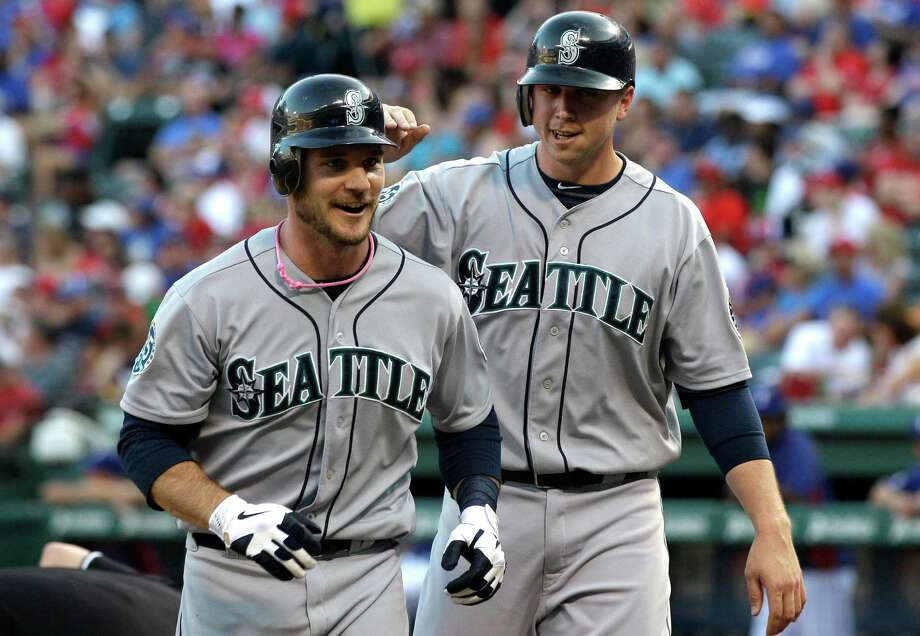 John Jaso (left), Justin Smoak and the Mariners snapped a five-game skid against Texas. Photo: AP