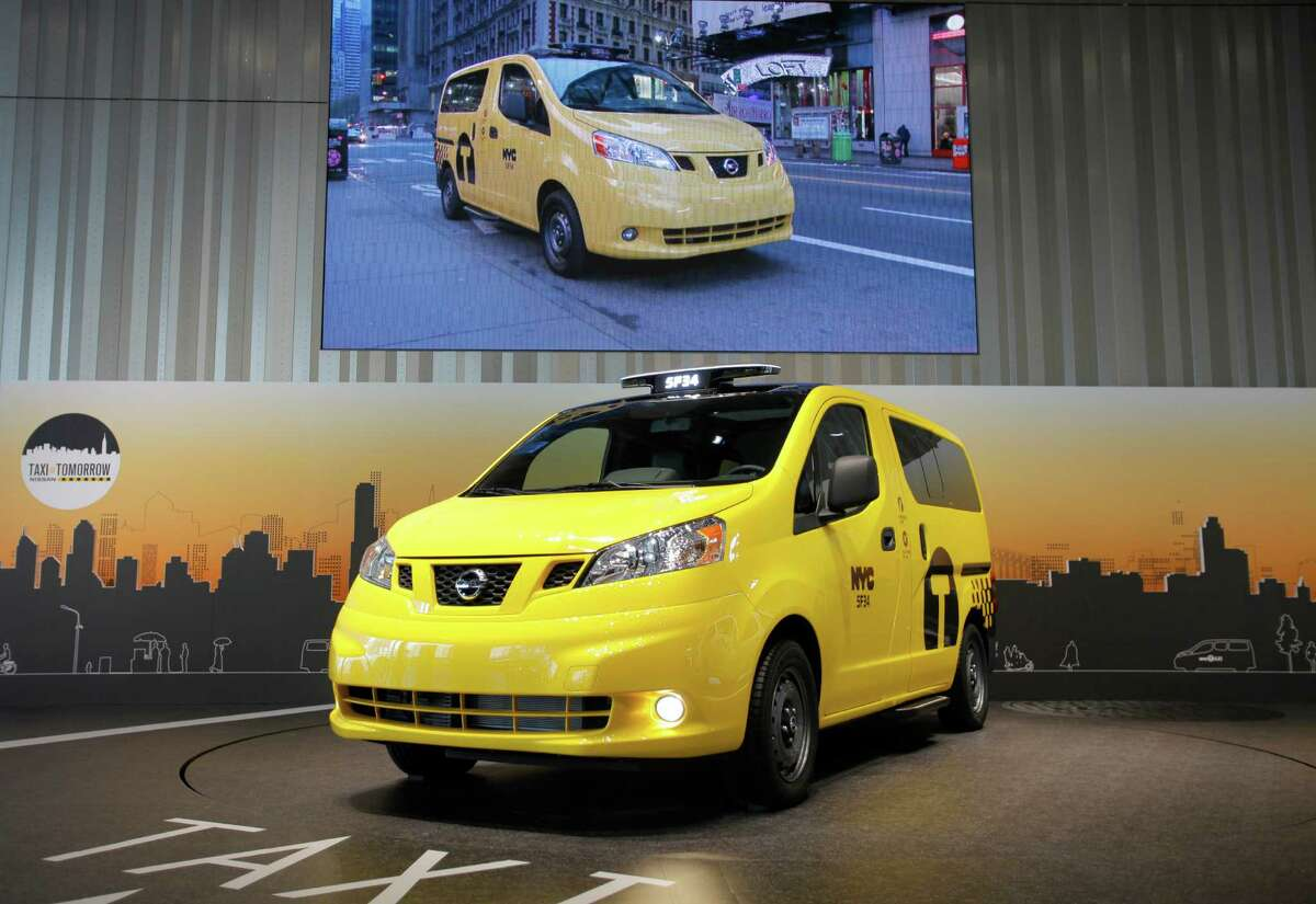 Nissan Motor Co.'s gas-engine NV200 vehicle is displayed at the automaker's headquarters in Yokohama, near Tokyo, Tuesday, May 29, 2012. The NV200 vehicle is set to start running as New York taxis in October 2013. Nissan is supplying New York City with fuel-efficient cabs, including six electric cars for testing, but acknowledged uncertainties Tuesday about an ongoing