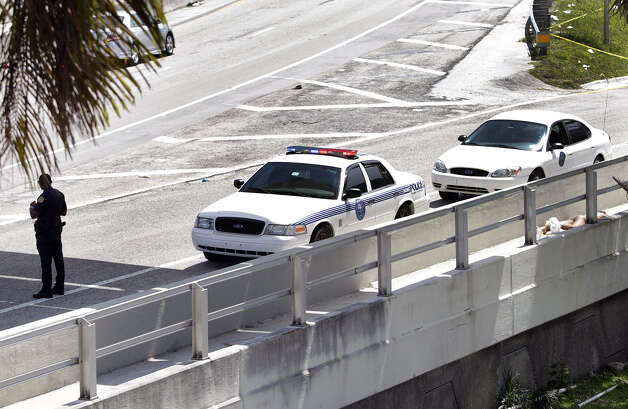 A City of Miami police officer stands watch near the scene where a naked man, far right, was shot dead on the MacArthur Causeway ramp onto Northeast 13th Street in Miami on Saturday, May 26, 2012. A witness said the naked man continued to chew on the face of another naked man on a Miami highway ramp and growled when a police officer tried to stop him. The victim remained hospitalized Monday. (AP Photo/The Miami Herald, Marsha Halper)  MAGS OUT Photo: Marsha Halper