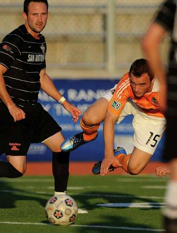 Cam Weaver of the Houston Dynamo (15) goes flying as Ryan Cochrane of the San Antonio Scorpions watches during U.S. Open Cup match action at Heroes Stadium on Tuesday, May 29, 2012. Photo: Billy Calzada, Billy Calzada / Express-News / © 2012 San Antonio Express-News