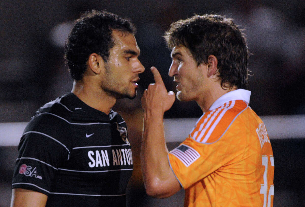 Pablo Campos (left) of the San Antonio Scorpions and Bobby Boswell of the Houston Dynamo have words after rough play during their match at Heroes Stadium on Tuesday, May 29, 2012.