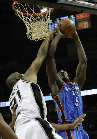 San Antonio Spurs' Tim Duncan (21) gets a hand on a shot by Oklahoma City Thunder's Serge Ibaka (9) during the first half of game two of the NBA Western Conference Finals in San Antonio, Texas on Tuesday, May 29, 2012. Kin Man Hui/Express-News (Kin Man Hui / San Antonio Express-News)