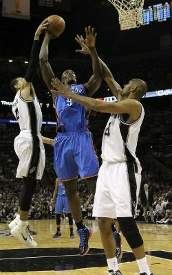 Oklahoma City Thunder's Serge Ibaka (9) shoots against San Antonio Spurs' Danny Green (4) and San Antonio Spurs' Tim Duncan (21) during the first half of game two of the NBA Western Conference Finals in San Antonio, Texas on Tuesday, May 29, 2012. Kin Man Hui/Express-News (Kin Man Hui / San Antonio Express-News)