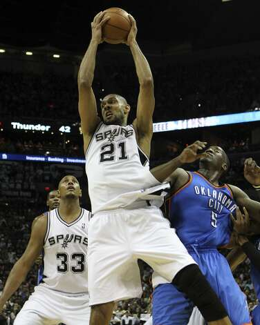 San Antonio Spurs' Tim Duncan (21) pulls in a rebound against Oklahoma City Thunder's Kendrick Perkins (5) and San Antonio Spurs' Boris Diaw (33) during the first half of game two of the NBA Western Conference Finals in San Antonio, Texas on Tuesday, May 29, 2012. Kin Man Hui/Express-News (Kin Man Hui / San Antonio Express-News)