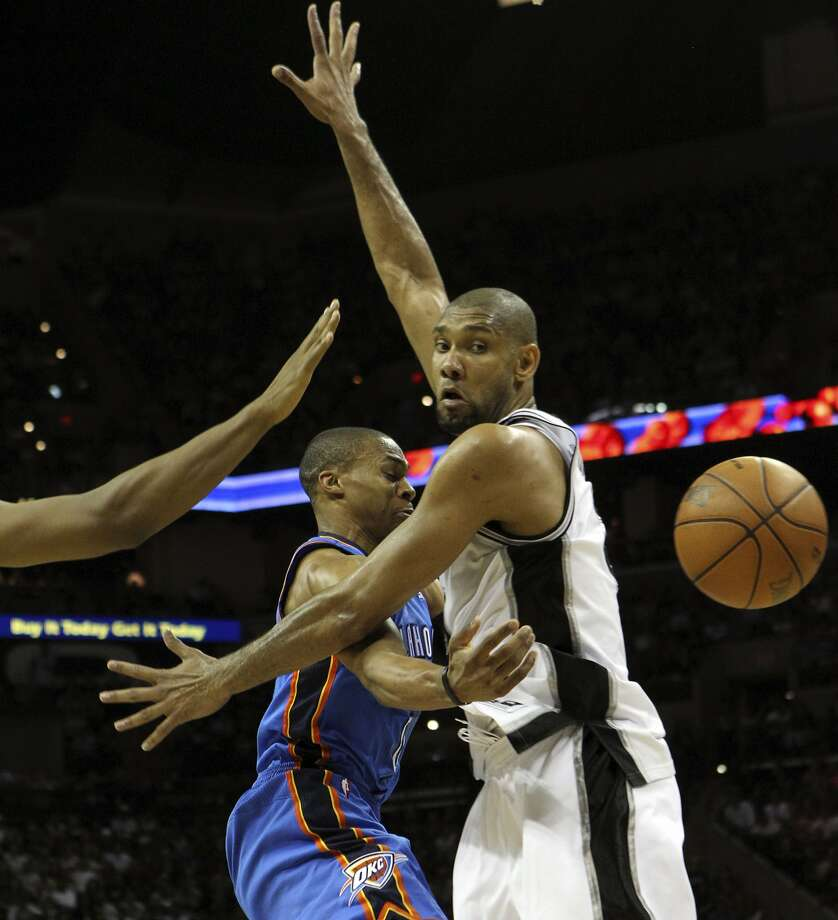 Oklahoma City Thunder's Russell Westbrook (0) passes around San Antonio Spurs' Tim Duncan (21) during the first half of game two of the NBA Western Conference Finals in San Antonio, Texas on Tuesday, May 29, 2012. Kin Man Hui/Express-News (Kin Man Hui / San Antonio Express-News)