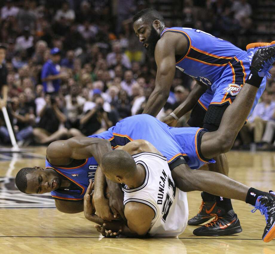 Oklahoma City Thunder's Serge Ibaka (9) fights for control of the ball with San Antonio Spurs' Tim Duncan (21) with Oklahoma City Thunder's James Harden (13) nearby during the first half of game two of the NBA Western Conference Finals in San Antonio, Texas on Tuesday, May 29, 2012.  Edward A. Ornelas/Express-News (Edward A. Ornelas / San Antonio Express-News)