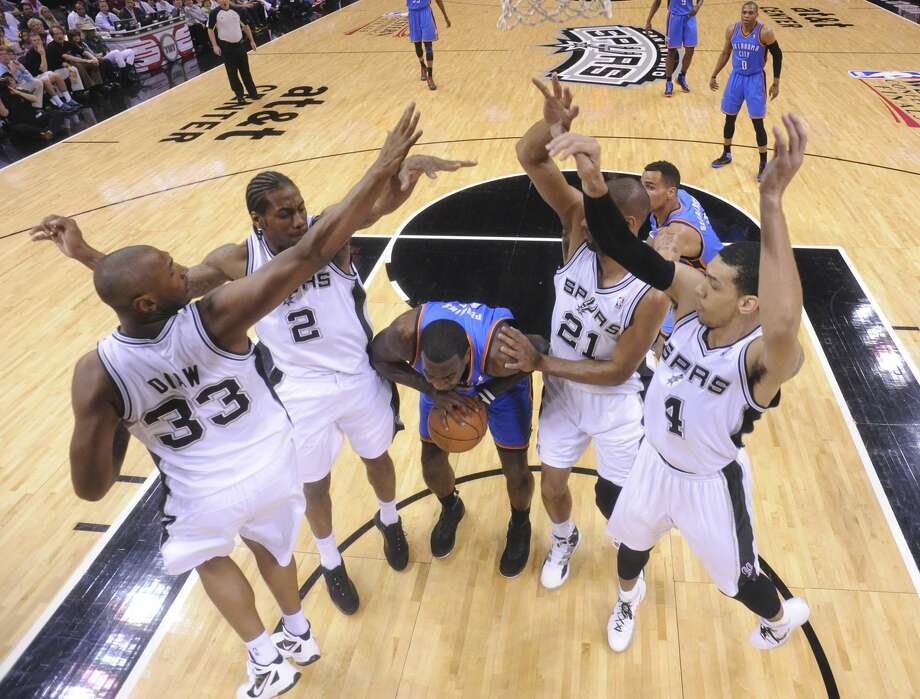 Oklahoma City Thunder's Kendrick Perkins (5) is under pressure from San Antonio Spurs' Boris Diaw (33), San Antonio Spurs' Kawhi Leonard (2), San Antonio Spurs' Tim Duncan (21) and San Antonio Spurs' Danny Green (4) during the first half of game two of the NBA Western Conference Finals in San Antonio, Texas on Tuesday, May 29, 2012.   Edward A. Ornelas/Express-News (Edward A. Ornelas / San Antonio Express-News)