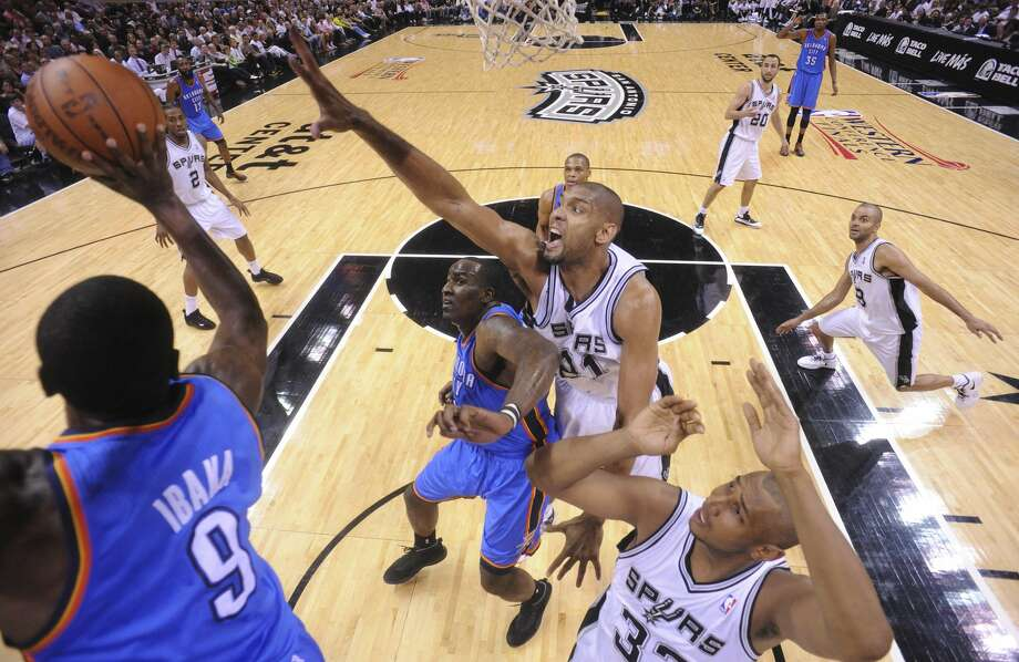Oklahoma City Thunder's Serge Ibaka (9) passes under pressure from San Antonio Spurs' Tim Duncan (21) during the first half of game two of the NBA Western Conference Finals in San Antonio, Texas on Tuesday, May 29, 2012.  Edward A. Ornelas/Express-News (Edward A. Ornelas / San Antonio Express-News)