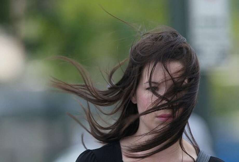 Zada Cotterman walks through Downtown Houston as winds reach 30 mph on Thursday, May 24, 2012, in Houston. Temperatures in the 90's today, with 30 mph winds are forecasted for today. (Mayra Beltran / Houston Chronicle)