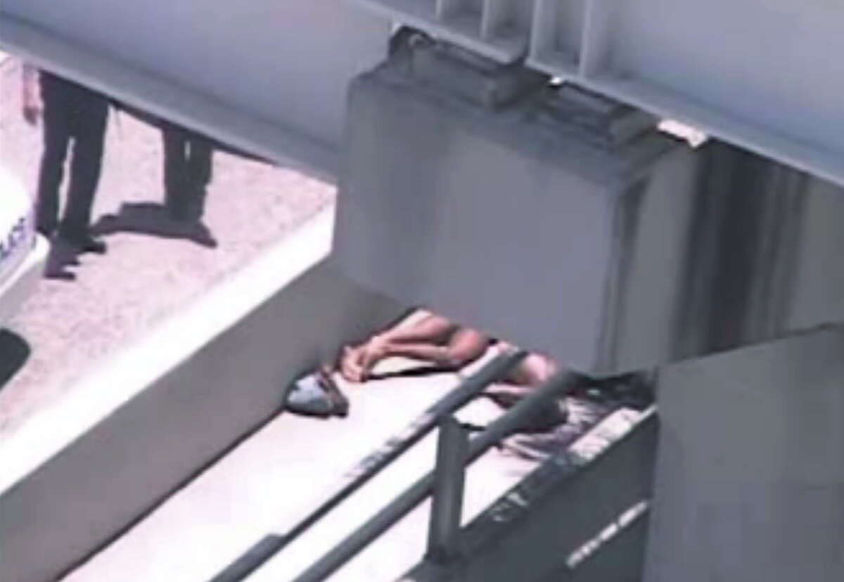 In this image taken from video, Miami police officers stand watch near a naked man, second from right, who was shot dead by a police officer when he refused to stop chewing on the face of the naked man next to him, partially obscured by a railing, on the MacArthur Causeway ramp onto Northeast 13th Street in Miami, Saturday, May 26, 2012. The victim was taken to a nearby hospital. Police say neither man's identity is known. (AP Photo/The Miami Herald) MAGS OUT