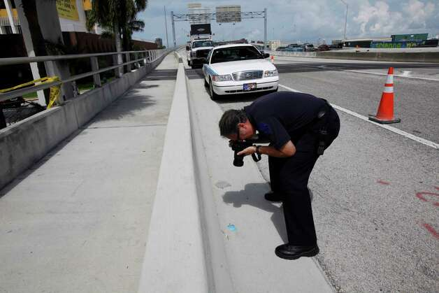 Crime Scene investigator Andres Betancourt photographs a credit card found at the scene belonging to Rudy Eugene, Tuesday, May 29, 2012 in Miami. Authorities were seeking more witnesses Tuesday to help explain what led Eugene, who was naked, to start chewing another naked man's face and whose only response when confronted by police was to growl and keep attacking - even after being shot by police Saturday. Photo: Wilfredo Lee, AP / AP