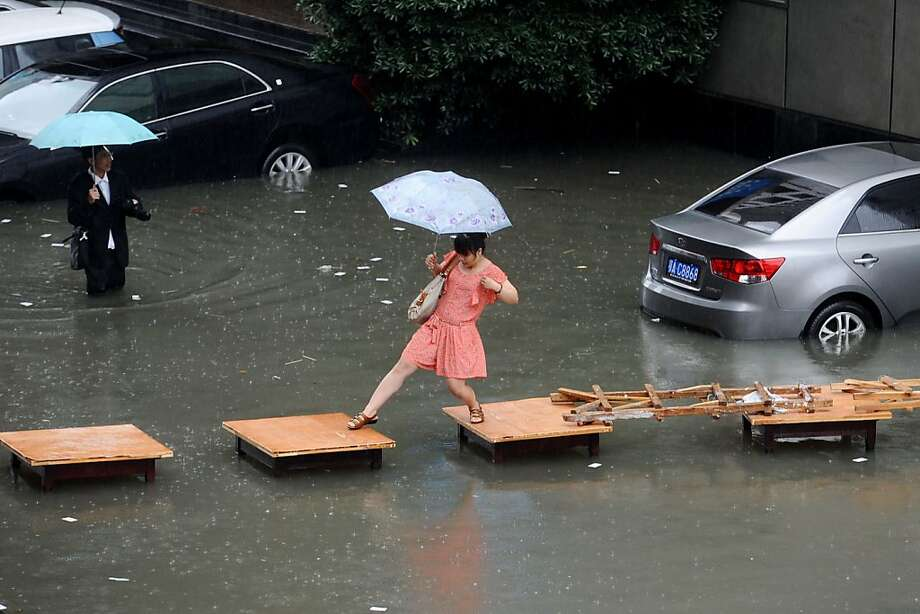 Table top hop:In Wuhan, China, a woman crosses a flooded street on a bridge of tables. Every summer, heavy downpours inundate China, often triggering flooding and landslides. Photo: Afp, AFP/Getty Images
