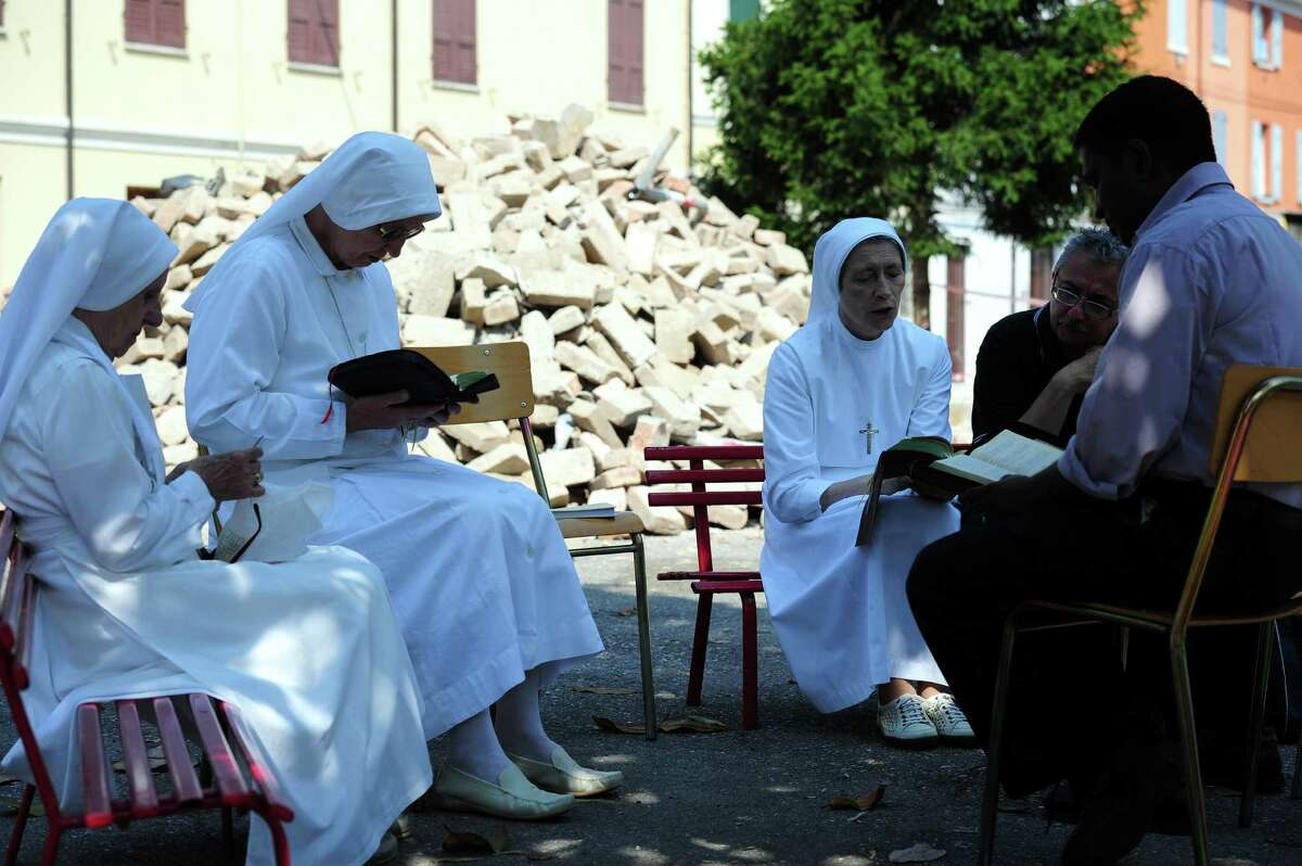Nuns and priests pray near rubble after an earthquake Wednesday in Mirandola. Dozens of aftershocks hit northeastern Italy overnight as thousands of jittery survivors spent the night in tent camps after the region's second killer quake in days. (OLIVIER MORIN/AFP/GettyImages)