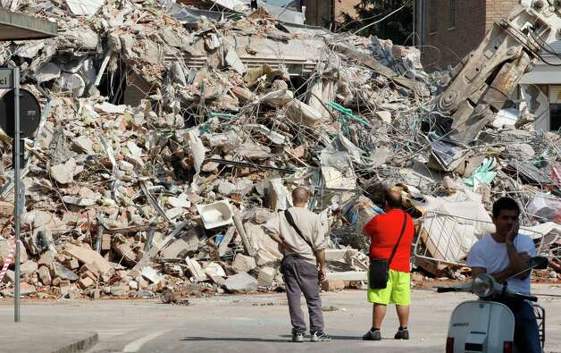 People stand in front of a collapsed building in Cavezzo, northern Italy, Wednesday, May 30, 2012. A magnitude 5.8 earthquake struck that felled old buildings as well as new factories and warehouses in a swath of Italy north of Bologna. The quake, which followed a May 20 magnitude-6.0 quake in the same area, dealt another blow to one of the country's most productive regions at a time when Italy is struggling to restart its economy. Photo: Luca Bruno, AP / AP2012