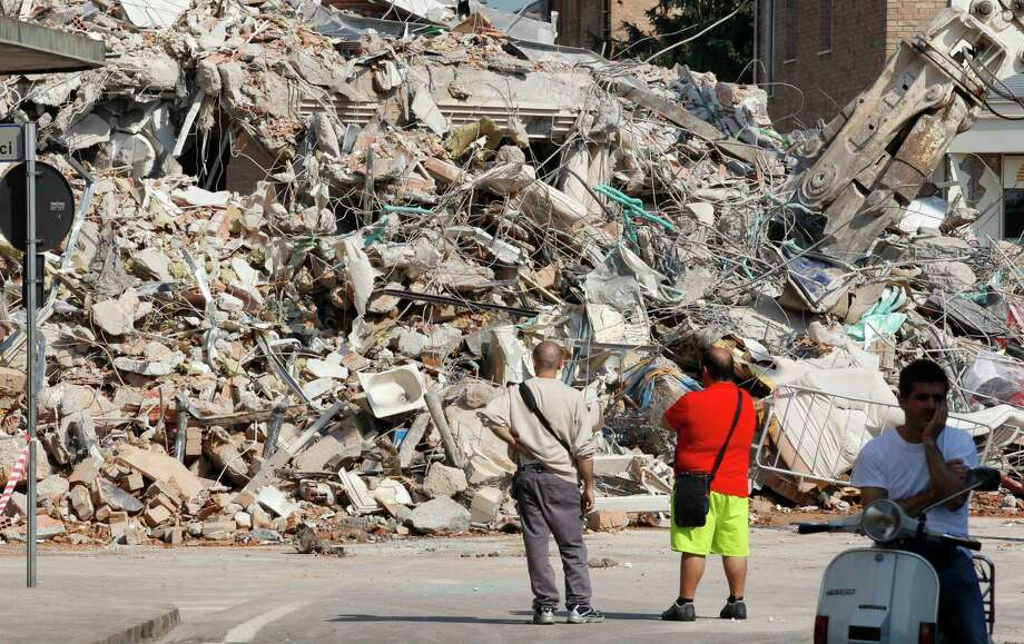 People stand in front of a collapsed building in Cavezzo, northern Italy, Wednesday. A magnitude 5.8 earthquake struck Tuesday that felled old buildings as well as new factories and warehouses in a swath of Italy north of Bologna. The quake, which followed a May 20 magnitude-6.0 quake in the same area, dealt another blow to one of the country's most productive regions at a time when Italy is struggling to restart its economy. Photo: Luca Bruno, AP / AP2012