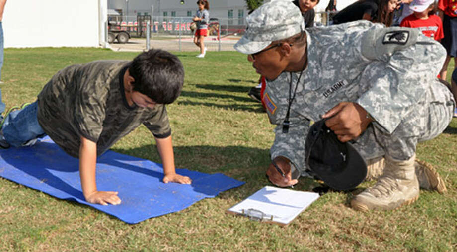 Sgt. Kelsey Curtis, of the 717th Military Intelligence Battalion, encourages a Columbia Heights Elementary School third-grader to pump out as many pushups as he can during the school's May 17 field day. Photo courtesy of Gregory Ripps