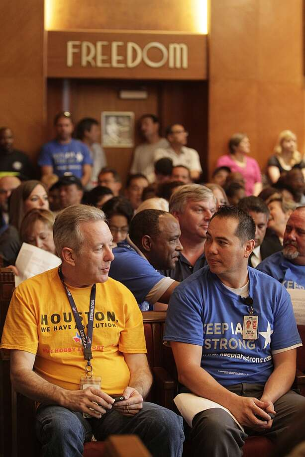 Scott Williams, Southwest employee, speaks Wednesday with Tuan Kincaid, United employee, minutes before Houston City Council voted on the Hobby Airport expansion.  Photo: Mayra Beltran, Houston Chronicle