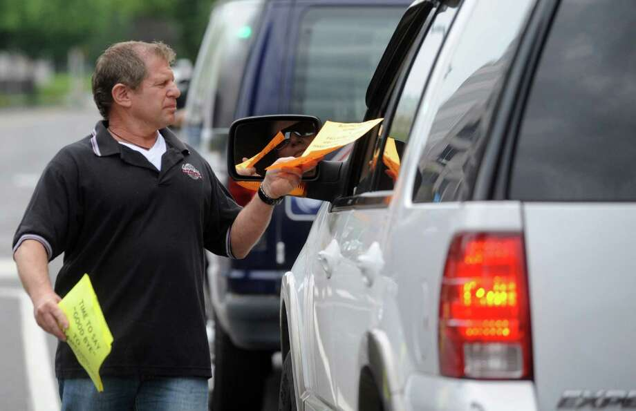 Lenny Corrente hands a flyer to a driver during a red light in front of Government center during a protest by Connecticut contruction workers and Laborers' Union members regarding Harbor Point on Wednesday, May 30, 2012. Photo: Lindsay Niegelberg / Stamford Advocate