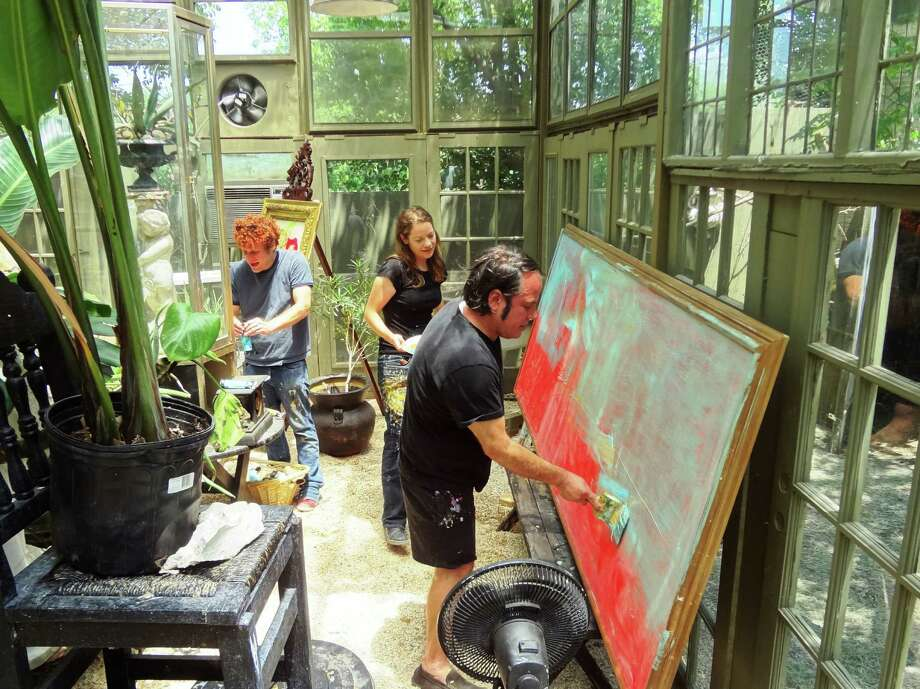 "In a sweltering greenhouse constructed of cast-off windows, San Antonio artist Franco Mondini-Ruiz repaints an large canvas with his assistants Bryson Brooks and Holly Hein Brooks. The large canvas is being repurposed into a landscape in homage to early Texas painters the Onderdonks. It's christened ""Big Ol' Donk."" Photo: Photo By Steve Bennett"