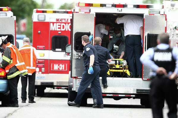 A victim is placed in an ambulance after five people were shot at Cafe Racer on Roosevelt Way NE in Seattle on Wednesday, May 30, 2012. Two of the victims died at the scene.  (Joshua Trujillo, seattlepi.com)