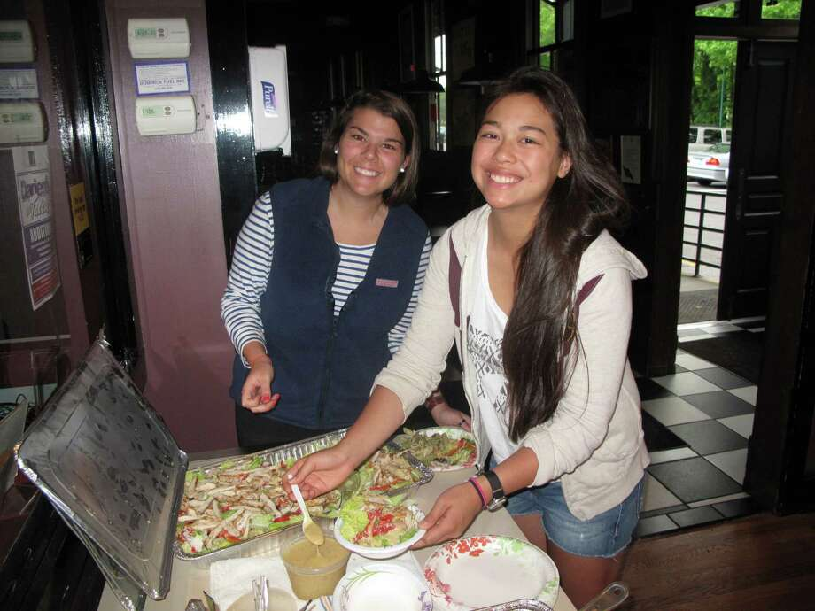 Sloane Clarke and Emily Caccam, members of Students Against Destructive Decisions, grab some food to celebrate SADD's end-of-the-year party at The Depot, Darien's Teen Center, Wednesday, May 23, 2012. Darien, Conn. Photo: Thomas Michael