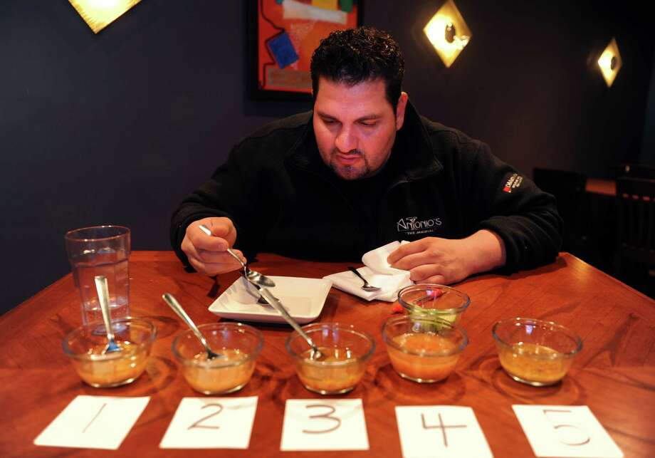 Chef and co-owner, Christian Setaro, tests five samples of bottled Italian salad dressing at his restaurant, Antonio's Friday, May 11, 2012.  Judging was based on appearance, texture and taste. Photo: Autumn Driscoll / Connecticut Post